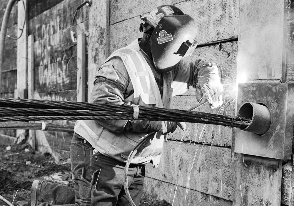 A worker welding a tie-back anchor